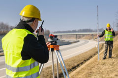 two surveyors surveying land beside a highway