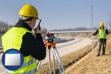 land surveyors surveying a highway with Wyoming map icon