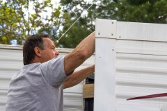 man repairing mobile home siding