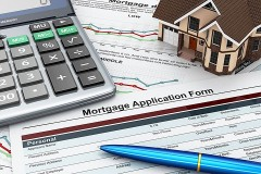 mortgage application with pen, calculator, and miniature model home