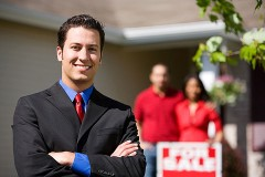 smiling real estate agent in front of a blurred house and couple