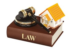 miniature model home and gavel atop a law book