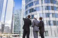 men pointing at a modern office building