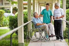 senior citizen in a wheelchair, with nurse and visitor