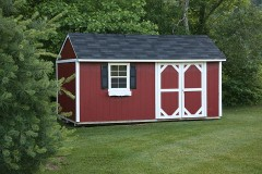 a storage shed at the edge of a lawn
