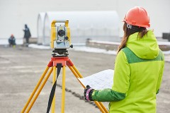 female surveyor with land surveying level and tripod